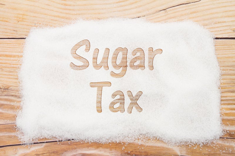 """white sugar spread on wood with the words """"sugar tax"""" written in it"""