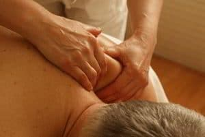 photo of man laying on his stomach having deep sports massage treatment on his shoulder