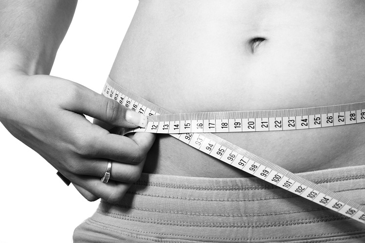 Image of female measuring a bare stomach with tape measure to check the effect of the weight loss service offered by David Marshall Personal Training based in Northampton